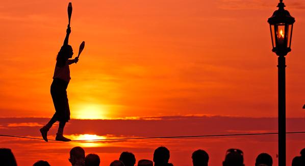 Will Soto juggles while balancing on the tightrope at the Mallory Square sunset celebration. Photo: Bob Krist/Florida Keys News Bureau